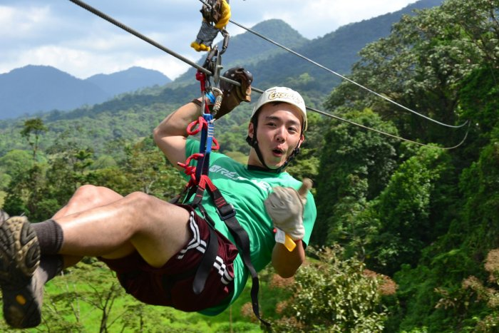 A young man giving a thumbs up while on a zipline cable | Arenal EcoGlide Canopy Tour