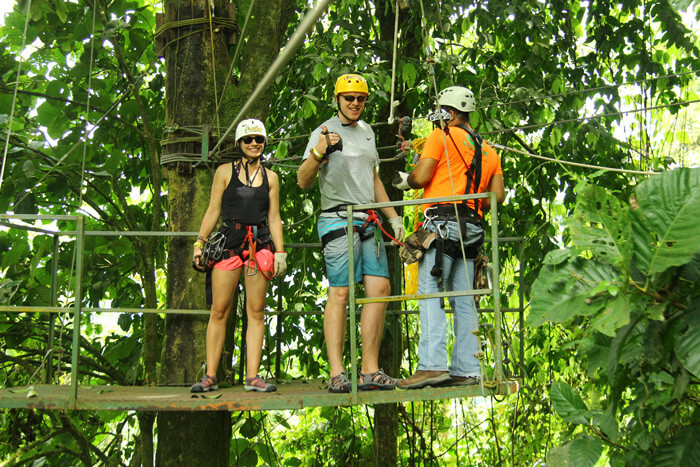 Arenal EcoGlide CanopyTour Guide standing on a treetop platform with two happy looking customers