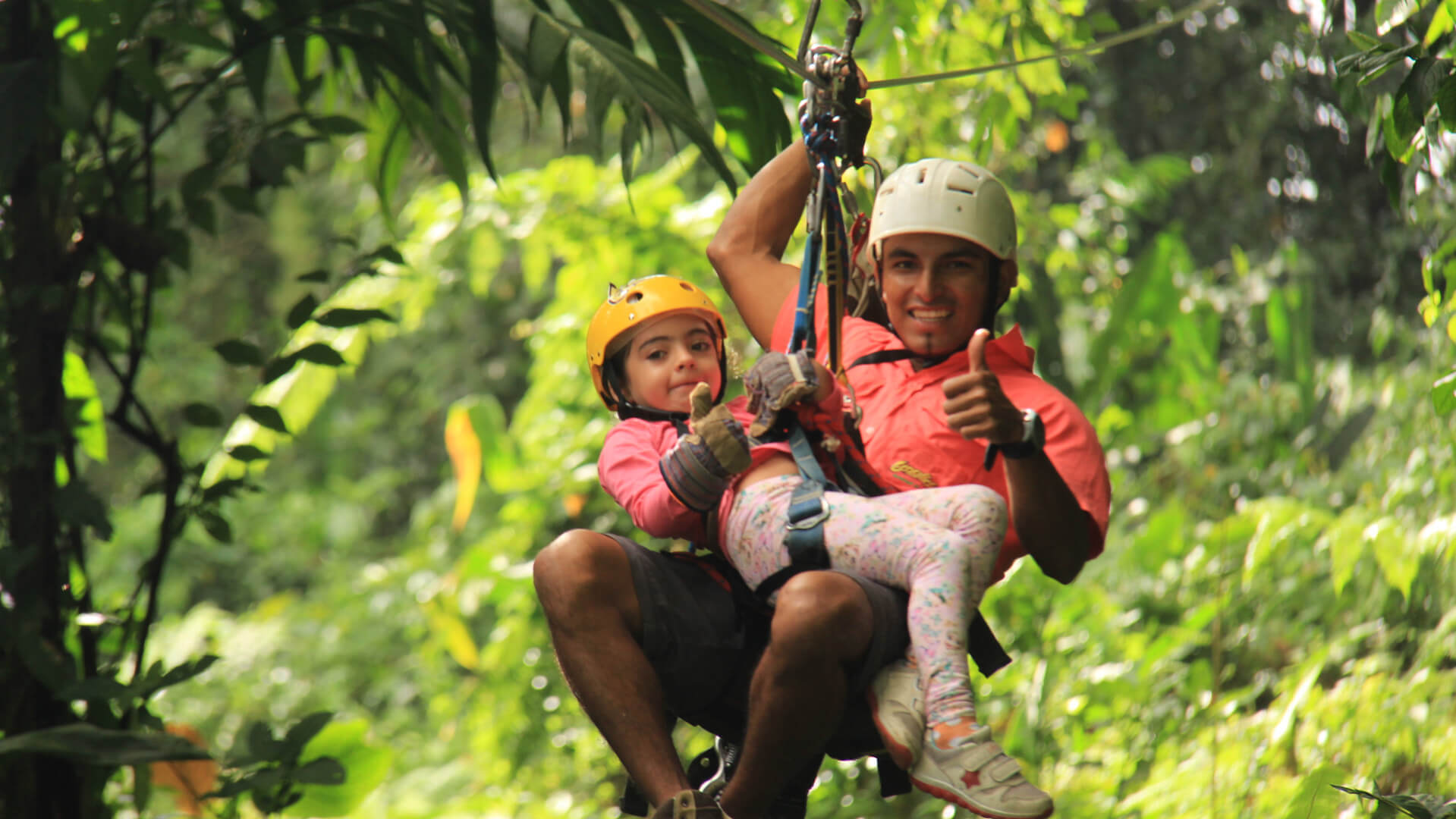 A child zipping in Tandem with a guide at the Arenal Ecoglide Canopy Tour