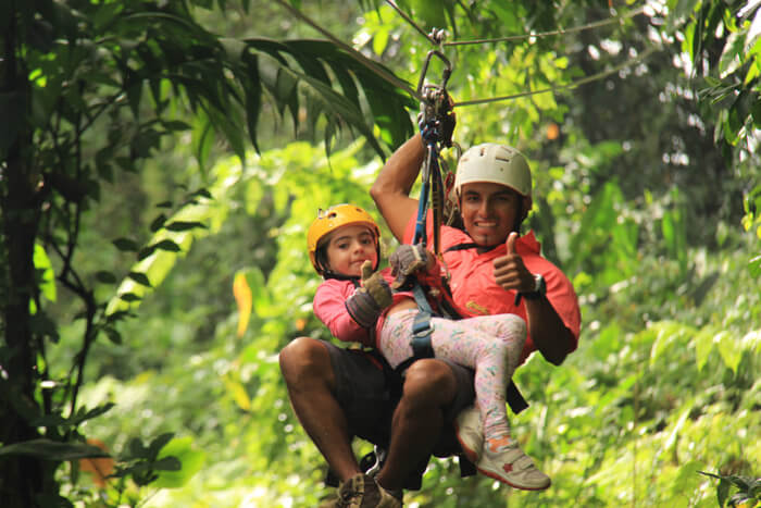 Arenal EcoGlide Canopy Tour Guide on a zipline in tandem with a young girl - Arenal Volcano Area